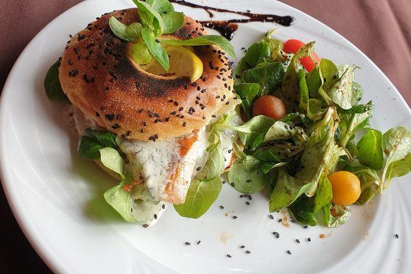 Bagel au pavot chaud, tomate, saumon snacké à la plancha, crème d'aneth, citron, accompagné de mâche