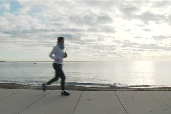 Une joggeuse en train de courir sur la promenade de Cagnes-Mer.