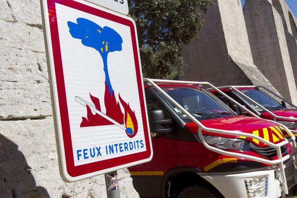 """Un panneau """"feux interdits"""" à côté de camions de pompiers - Photo d'illustration"""