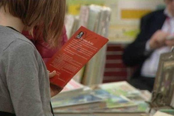 Une jeune lectrice dans les allées du festival du livre de jeunesse de Rouen en 2012