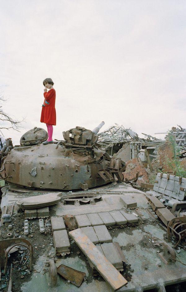Petite fille tchétchène sur un char russe détruit par les Boevikis (combattants tchétchènes). Grozny, Tchétchénie, 1996.