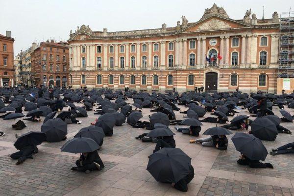 """Tous habillés de noir et équipés d'un parapluie, les 800 manifestants ont participé à une """"performance revendicative et artistique"""" place du Capitole."""