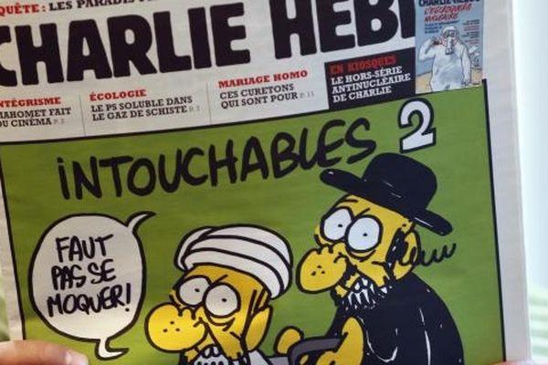 """Un homme regarde les caricatures du prophète Mahomet parues dans le numéro de """"Charlie Hebdo"""" daté du 19 septembre 2012, à Paris"""