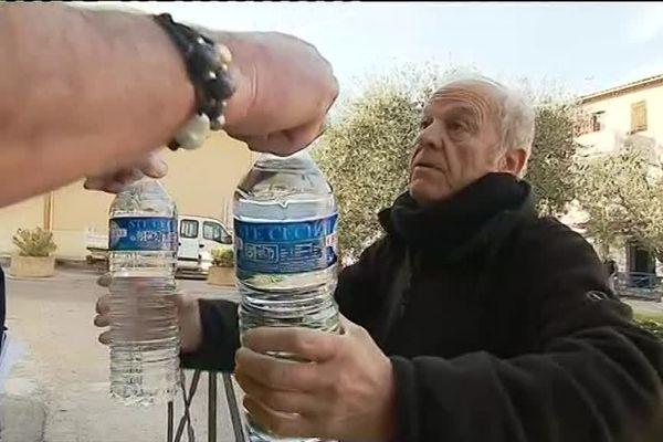 Un habitant de Tourrette-Levens reçoit des bouteilles d'eau lors d'une distribution.