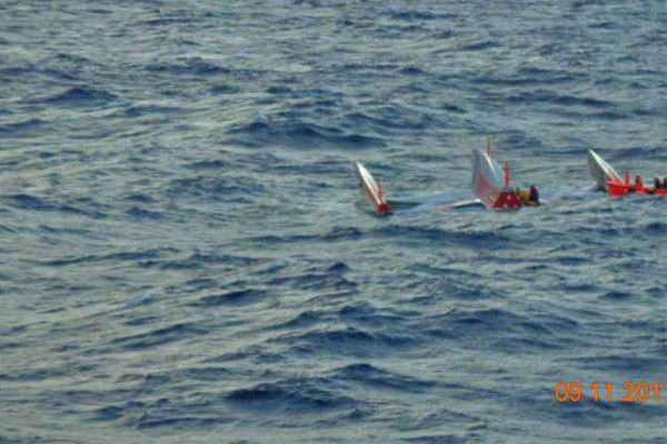 Un canot du cargo est envoyé sur le trimaran chaviré pour embarquer les deux skippers