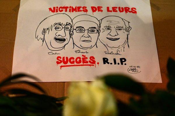 Photo prise le 7 janvier 2015 devant l'ambassade de France à Berlin (Allemagne), présentant les caricaturistes Cabu, Charb et Wolinski.
