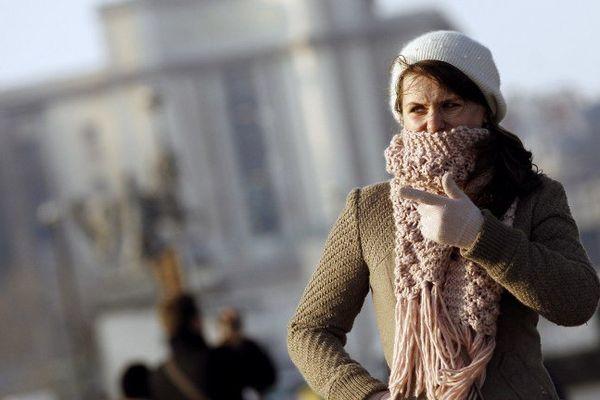 Une femme se protégeant du froid à Paris.