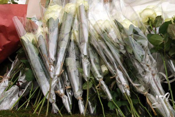 Un hommage avec des roses blanches (illustration).