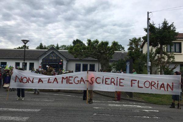 """Lannemezan - 29 mai 2021. Les manifestants portent une grande banderole """"Non à la méga-scierie Florian""""."""