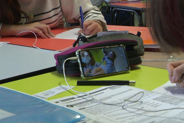 Les élèves suivent les cours en binôme grâce aux téléphones portables.