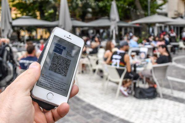 Un téléphone affichant un pass sanitaire devant une terrasse de restaurant, le 8 août 2021.