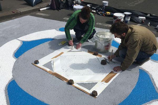 Anne-laure et Gomm du collectif A Part réalisent un mandala sur un sas vélo à Rennes