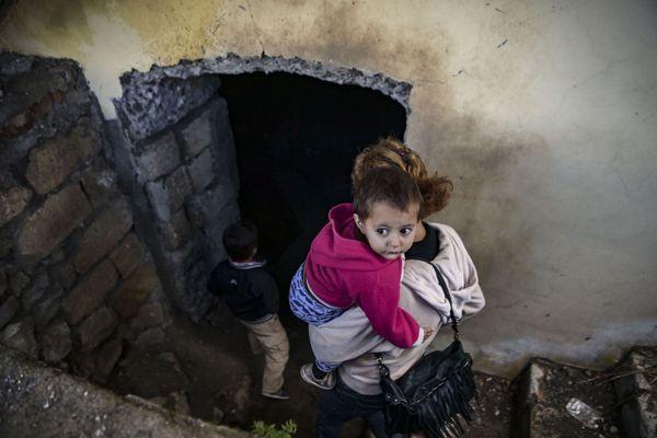 Une femme porte son enfant dans un abri en sous-sol dans la ville historique de Shusha, en Arménie, le 8 octobre 2020
