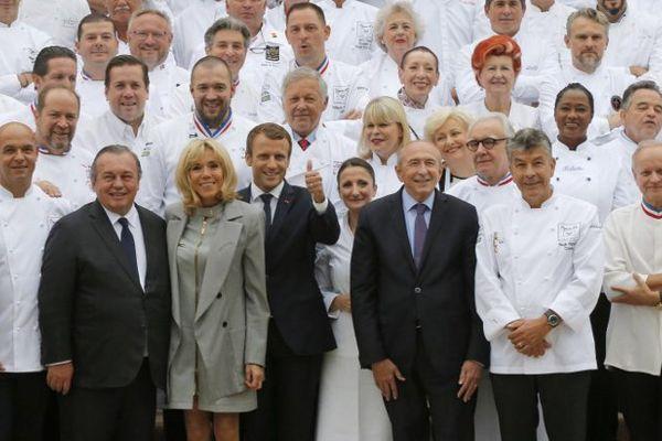 De gauche à droite : Jérôme Bocuse, Olivier Ginon, Brigitte Macron, Emmanuel Macron, Gérard Collomb, Régis Marcon et Joël Robuchon. Ils sont réunis à l'Elysée le 27 septembre 2017 où 180 chefs étaient invités pour promouvoir la cuisine française.