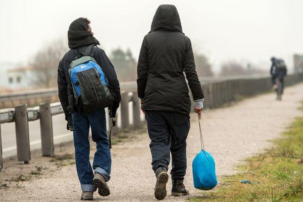 Des migrants marchant le long d'une route à Calais.