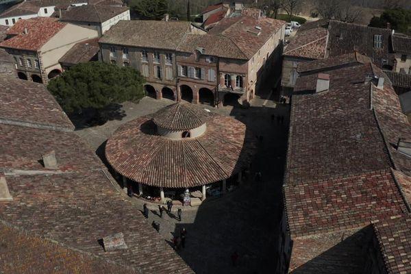 Une superbe halle aux grains circulaire trône sur une place pavée bordée de maisons à arcades.
