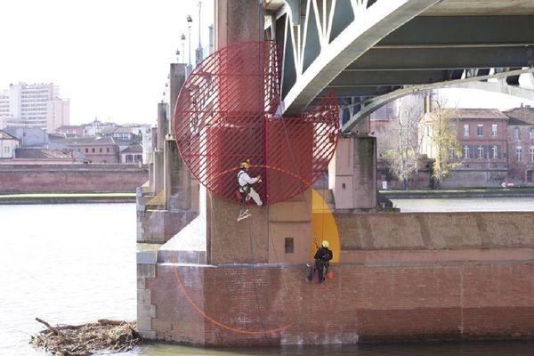 Les cordistes-acrobates tracent le cercle jaune sur la pile du Pont-St-Pierre.