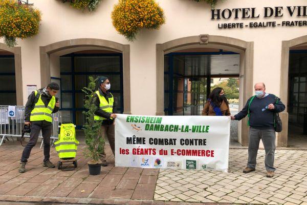 Les opposants d'Amazon ont fait converger leurs luttes ce 2 octobre devant l'hôtel de ville d'Ensisheim (Haut-Rhin)