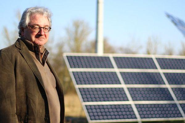 alain Bessero, devant les panneaux solaires qui alimentent, avec une éolienne, sa maison en électricité