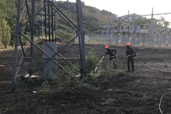Les sapeurs-pompiers arrosent les abords des pylônes électriques pour éviter toute reprise de l'incendie.