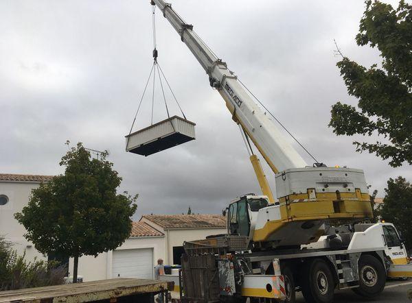 La piscine container est grutée par dessus la maison pour être posée chez le client.