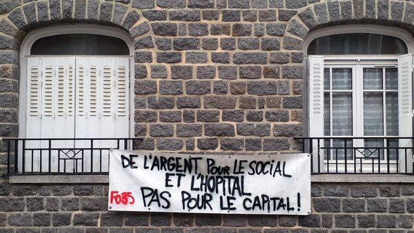 Un slogan sur une banderole entre deux balcons  à Rennes