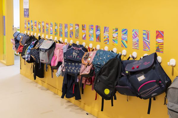 Des cartables alignés dans un couloir d'école primaire.