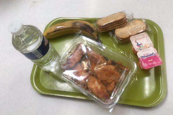 Plateau repas avec une bouteille d'eau, une banane, deux sachet de gâteaux secs, deux yaourt et une barquette avec poulet et petits pois.
