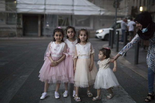 En ce 26 mai 2020, alors que la France lève progressivement son confinement en raison de la COVID-19, une mère fait poser ses enfants vêtues de robes de fête dans la rue au cours d'une promenade nocturne à Marseille.