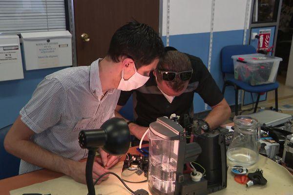 Deux bricoleurs de l'association Repair Café Tours s'attèlent à la réparation d'une cafetière.