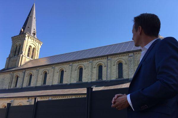 Guillaume Coutey, le maire de Malaunay, devant l'église de sa commune équipée de panneaux photovoltaïques