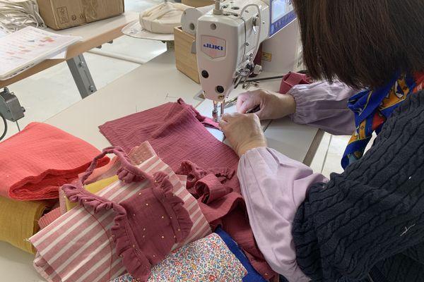 Une salariée de l'association Mode Estime confectionnant les habits d'une poupée. Crédit photo Elie SAIKALI
