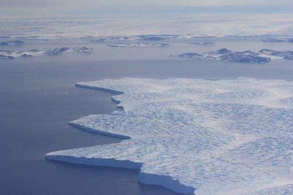 Langue glaciaire flottant sur la mer, près de la base australienne de Casey en Antarctique (décembre 2014). A l'arrière-plan, on distingue quelques îles et la calotte antarctique.