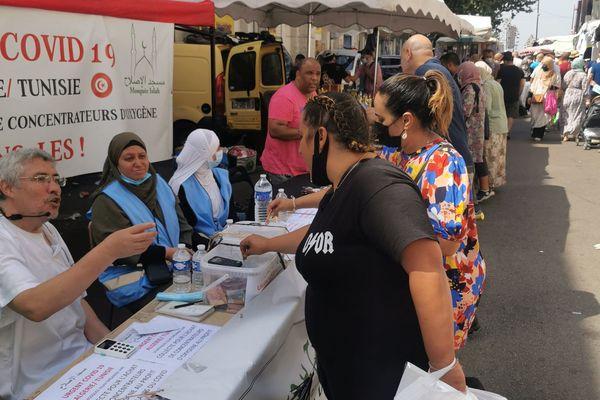 Deux femmes donnent de l'argent pour la collecte de dons en Algérie et en Tunisie. La somme totale permettra d'acheter des concentrateurs d'oxygènes.