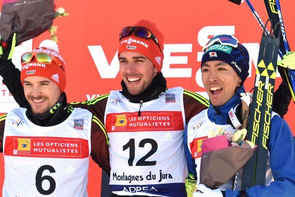De gauche à droite sur l'image : les Allemands Fabian Riessle (2ème sur le podium), le vainqueur Johannes Rydzek, et le Japonais Akito Watabe (3ème)
