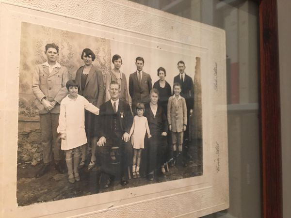 Jeanne (la deuxième, en haut à gauche) et ses huit frères et sœurs posent avec leurs parents.