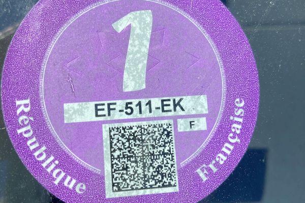 Le certificat se présente sous la forme d'un autocollant rond et correspond à une classe de véhicule définie en fonction des émissions de polluants atmosphériques.