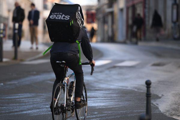 Un livreur à vélo Uber Eats lors d'une livraison.