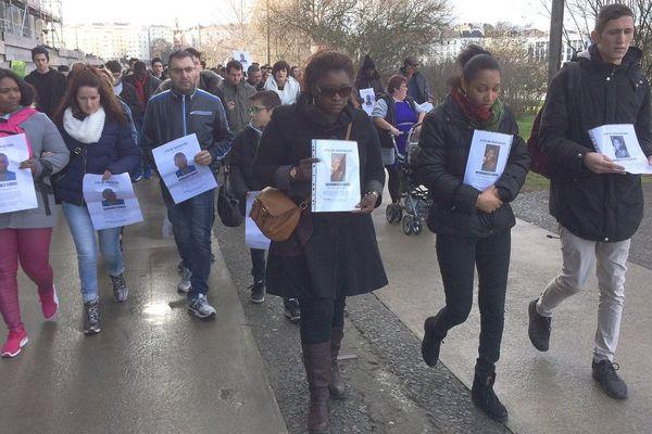 """Des participants à la """"promenade de soutien"""" arborent le portrait de Mouhamed"""