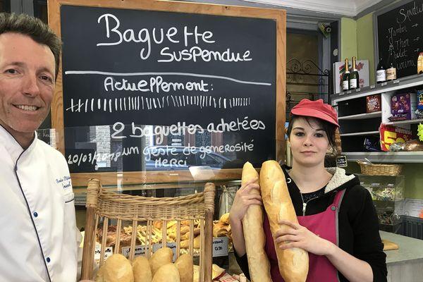Christophe Ponseel et son employée, Anaïs Geneviève, devant l'ardoise indiquant la règle et le nombre de baguettes suspendues.