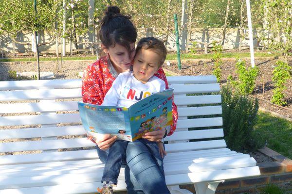 Marina et Yanis avec le petit livret dans leurs mains sur un banc.