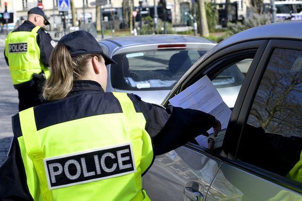 Des policiers contrôlent les voitures place de Bretagne à Rennes afin de vérifier si les passagers ont leur attestation de déplacement.
