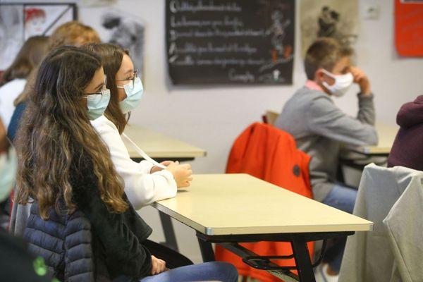 Illustration. Des collégiens portent un masque pendant un cours.
