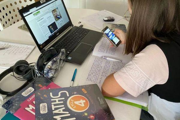Une élève de collège en train de réviser chez elle.