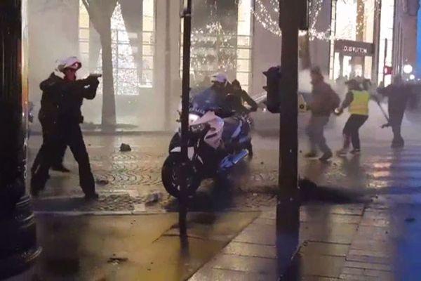 Samedi 22 décembre en fin de journée, un motard de la police pointe son arme face à la foule, pris à partie par des manifestants, alors que les forces de l'ordre tentent d'évacuer les Champs-Elysées.