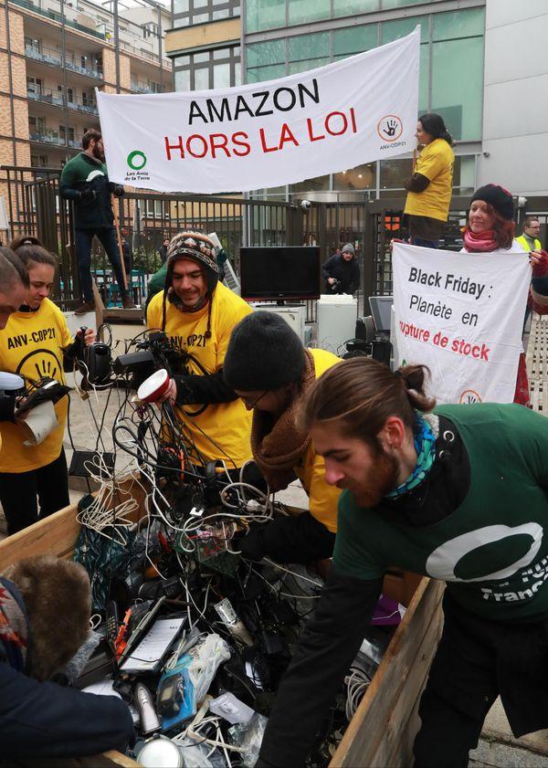 Des activistes des ONG Les Amis de la Terre et ANV Cop21 déversent de déchet devant le siège français d'Amazon, en novembre 2018.