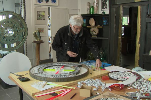 Paul Gonez dans son atelier, l'oeuvre a été réalisée à plat avec des centaines de flacons de vaccins contre le covid.