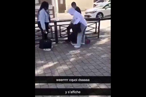 Une jeune fille à terre, victime de coups de pieds de la part d'un garçon, à la sortie du collège à Reims.