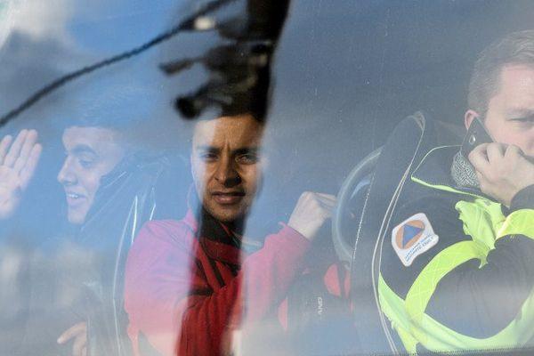 """Le 2 novembre, un membre de la Sécurité Civile accompagne des migrants mineurs quittant la """"jungle"""" de Calais pour des centres d'accueil situés dans des régions françaises."""