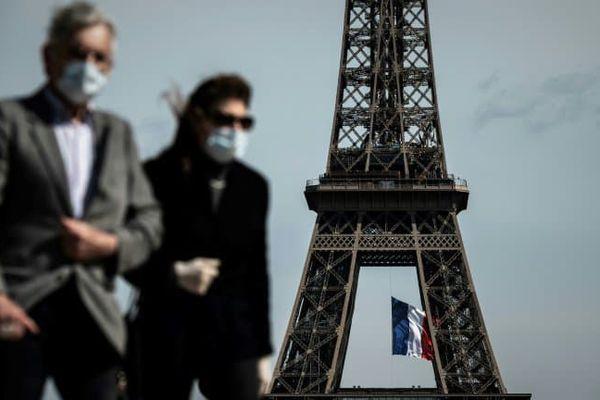 Homme et femme portant un masque devant la Tour Eiffel à Paris (photo d'illustration) - PHILIPPE LOPEZ © 2019 AFP
